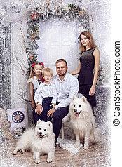 Familia con dos perros blancos cerca del árbol de Navidad