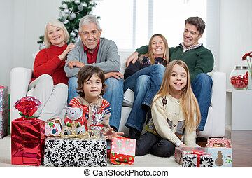 Familia con regalos de Navidad en casa