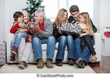 Familia con regalos de Navidad sentados en casa