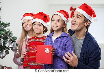 Familia en sombrero de Santa con regalo de Navidad