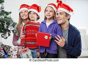 Familia en sombreros de Santa con regalo de Navidad