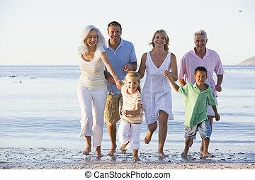 Familia extendida caminando por la playa