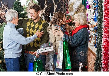 Familia feliz abrazando en la tienda de Navidad