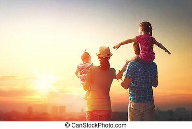 Familia feliz al atardecer.