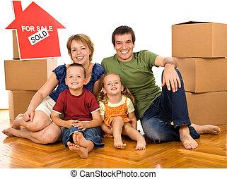 Familia feliz con cajas de cartón moviéndose en un nuevo hogar
