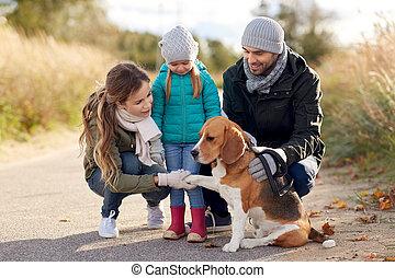 Familia feliz con perro sabueso al aire libre en otoño