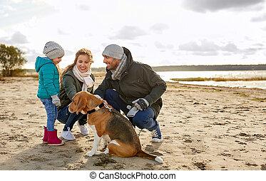 Familia feliz con perro sabueso en la playa