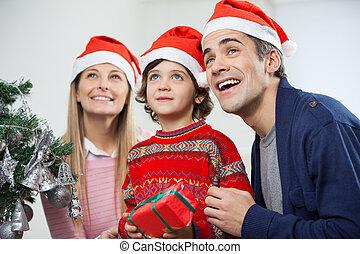 Familia feliz con regalo de Navidad mirando hacia otro lado