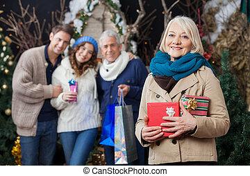 Familia feliz con regalos de Navidad en la tienda