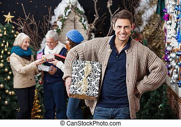 Familia feliz con regalos en la tienda de Navidad