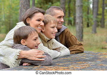 Familia feliz en el bosque de otoño