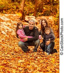Familia feliz en el bosque otoñal