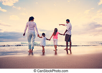 Familia feliz en la playa al atardecer