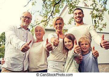 Familia feliz frente a casa al aire libre