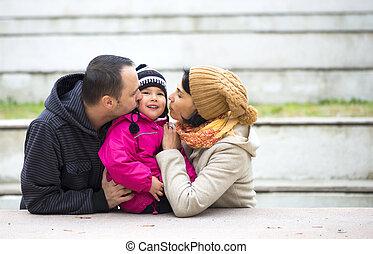 Familia feliz. Padres besando a su bebé. Mamá, papá y bebé.