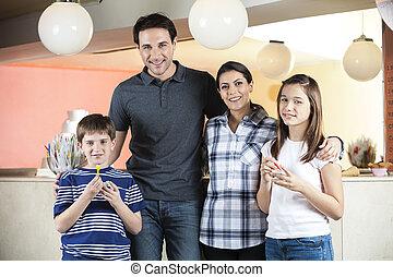 Familia feliz parada en la heladería