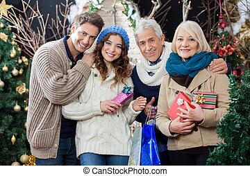 Familia feliz parada en la tienda de Navidad