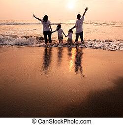 Familia feliz tomando de la mano en la playa y viendo el atardecer