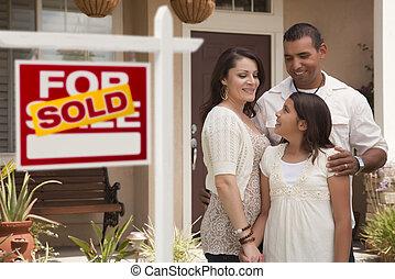 Familia hispana frente a casa con un cartel de bienes raíces vendido