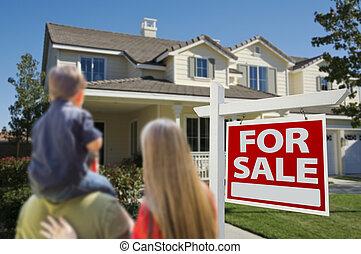 Familia mirando a un nuevo hogar con un cartel de venta