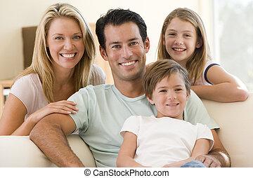 Familia sentada en la sala sonriendo