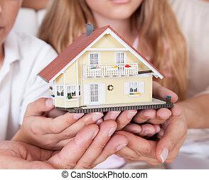 Familia sentada sosteniendo un modelo de casa en miniatura