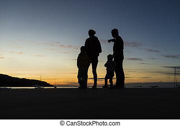 Familia silueta al aire libre mirando el atardecer