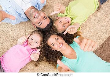 Familia sonriente tirada en la alfombra en un círculo mostrando pulgares arriba