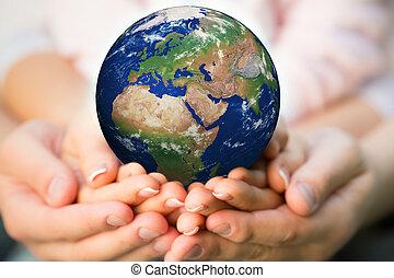 Familia sosteniendo planeta tierra