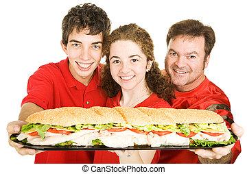 Fanáticos de deportes con un sándwich gigante