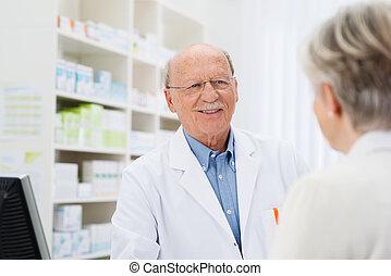 Farmacéutico hablando con un paciente mayor