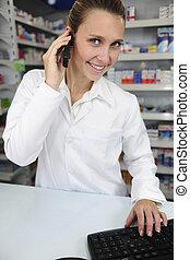 Farmacéutico usando computadora y teléfono