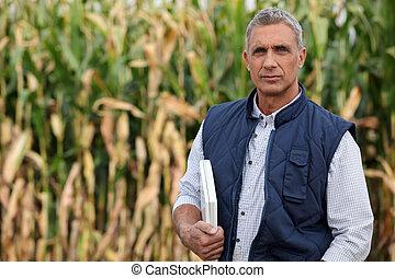 Farmer en un campo con una computadora portátil