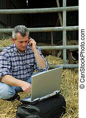 Farmer en un granero con su portátil