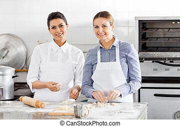 Felices chefs hembras preparando pasta en el mostrador