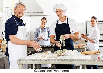 Felices chefs macho y hembra preparando pasta en la cocina