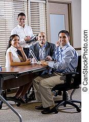 Felices empleados de oficinas reunidos en la mesa en la sala de juntas