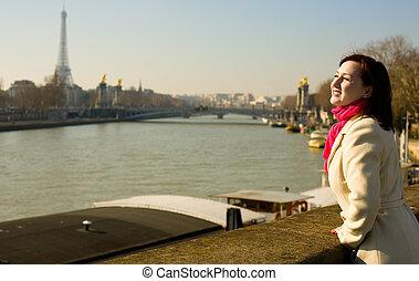 Feliz bella mujer en París en el terraplén Seine