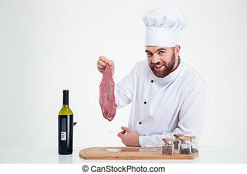 Feliz cocinero masculino sosteniendo carne fresca