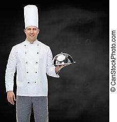 Feliz cocinero masculino sosteniendo cloche