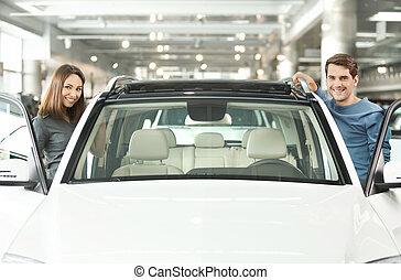 Feliz con su nuevo auto. Una feliz pareja joven a ambos lados del auto sonriendo a la cámara