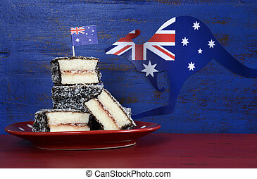 Feliz Día de Australia, enero 26, comida para fiestas con icónicas tartas australianas de lamington en un fondo de madera rústico negro y azul reciclado.
