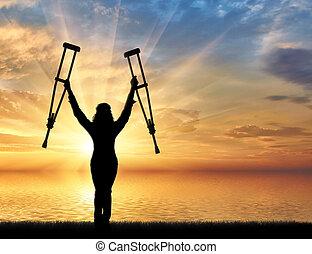 Feliz discapacitado en la playa y sosteniendo sus muletas al atardecer