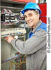 Feliz electricista trabajando en la caja de electricidad