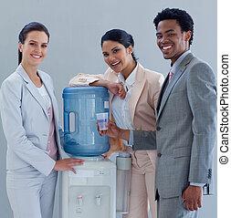 Feliz equipo de negocios con un refrigerador de agua en la oficina