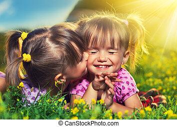 Feliz familia. Pequeñas gemelas besándose y riéndose al aire libre
