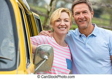 Feliz hombre de mediana edad y mujer pareja con caravana