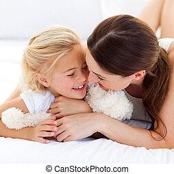 Feliz madre hablando con su hijita en la cama