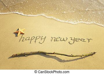 Feliz mensaje de año nuevo en la playa de arena