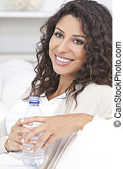 Feliz mujer hispana bebiendo agua